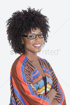 African american hair : Portrait of young woman in african print attire standing hands folded over gray background