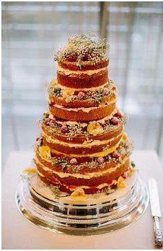 Naked wedding cake decorated with baby's breathe and flowers