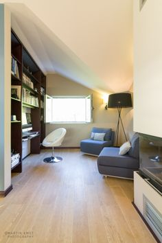Snug area, with large bespoke library, 2 convertible one-seater sofas from Soft Line. Fireplace. Cool lamp.
