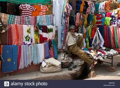 stallholder-selling-clothes-and-sari-fabrics-and-other-textiles-at-C8EH0X.jpg (1300×956)