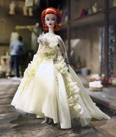 Barbie porte une création classique avec des détails floraux et une coiffure rouge, un dép...