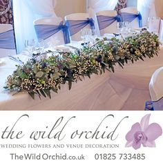 A garland decorates the top table for this winter themed wedding. The bride chose lots of lovely winter foliages, berries, trailing ivy, pussy willow with gypsophila and touches of blue thistle and white lisianthus.