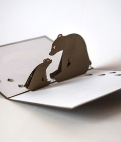 The brown cover of this Bears Pop Up Card features a mama or papa bear lovingly cradling a bear cub. Once opened this sweet card pops up to reveal a mama or papa bear playfully gazing at its baby cub. Plus