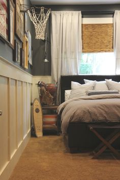 Teen Boy's Room - lower wall is Annie Sloan Old White, top of wall is Martha Stewart Seal, lights are Restoration Hardware with the cord running behind the curtain panel, wire basket on nightstand to store sports equipment, brown leather upholstered head & foot board, bamboo blinds, curtains made from drop cloths, wire pipe painted black for curtain rod