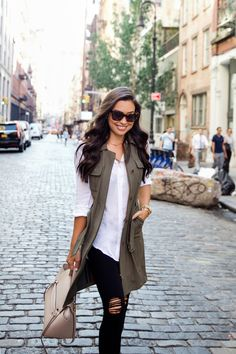 Fall outfit: army vest, white blouse, black distressed jeans, nude bag