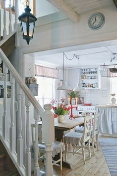 Pretty white country kitchen with dining spot and stairs to the upstairs. I always that a staircase in the kitchen would be so cool.