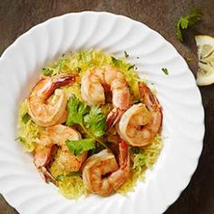 Garlicky shrimp are served on top of buttery, cilantro-flecked spaghetti squash in this quick, healthy dinner recipe inspired by shrimp scampi.