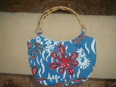 Bolsa feita em tecido azul, detalhe de flor vermelha e com alça em bambu...