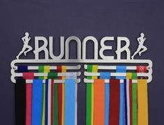 Wall-mounted medal display - male runner triple tier, in brushed stainless steel.