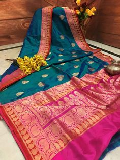 Show your iconic look as you deck up with this stunning Turquoise Blue and Hot Pink combination Silk Mark Certified pure Katan Banarasi Saree. Crafted from fine silk, this saree is extremely comfortable and flaunts traditional Banarasi Golden Zari work on the body and border. This saree also showcases glamorous Hot Pin
