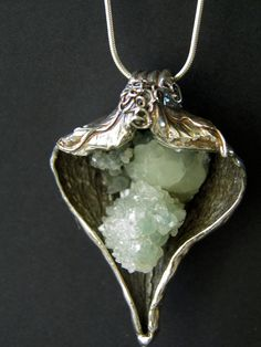 Artist used a milkweed pod to make this necklace with fine silver with a beautiful prehnite crystal in the center.