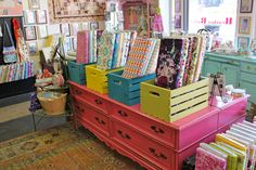 I love love that bright pink drawer and those  bright crates. Looking further to right, the aqua dresser matches perfectly also.