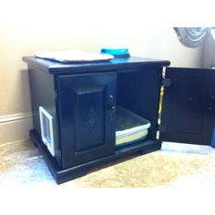 Converted this cabinet into a covered area for the cat litter box. Painted it and added the cat door.