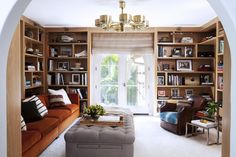 Modern brass fixture in a library will built-in bookshelves and leather armchair.
