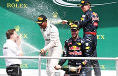 Hamilton celebrates by spraying champagne along with Red Bull's Ricciardo and third placed...