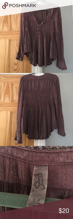 Free people purple flowy button up long sleeve This top looks worn but I haven't worn it more than twice. Super comfortable with buttons all the way up and a little bell sleeves. Do be warned the first three buttons leave a space in between where you can see your chest or bra. Could be avoided if you wore the right kind of bra that didn't show there Free People Tops Tees - Long Sleeve