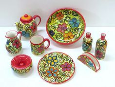 Conjunto de piezas de cerámica (jarra, taza, aceitera, platos, ensaladera...) pintado a mano. Set of handpainted pottery (jug, mug, plates, salad bowl...).