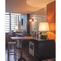 Na cozinha do designer de interiores Walter Fagundes Junior, este abajur verde foi herança de família e acolhe quem chega ao espaço. À frente dos azulejos garimpados ficam os eletrodomésticos: todos à disposição. A prancheta de desenho antiga, de ferro fundido, funciona como mesa para refeições rápidas. Foto Gui Morelli/Editora Globo @w___f_______jr #cozinha #decoração #abajurverde #mesapequena #azulejos