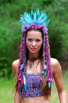 This flower feather headdress is sparkling with gems and purple pearls. Crowned with flowers, shades of blue, and teal feathers, shimmering aqua and
