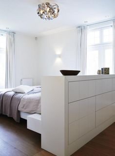 Woonmagazine bed midden, kast tegen muur en bed maakt aparte ruimte. Voor grote oppervlaktes