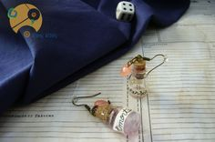 Adorables boucles d'oreilles fioles Philtre d'Amour, avec leurs perles coeurs rose corail, inspirées de la potion Amortensia dans le roman Harry Potter.  Si elles ne garantissent pas de rendre l'élu de votre coeur fou de vous, elles sauront cependant attirer les regards.  9,30 euros