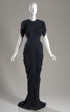 """""""La Sirène"""" Evening Dress, Charles James (1906-1978): 1941, silk crepe, satin-backed lining. """"James launched this mermaid-like gown early in his career and created several versions of it over a period of twenty years. The name of the dress, La Sirène, refers to sea creatures in Greek mythology who used their enchanting voices to lure sailors to their deaths. The soft folds cascading around the wearer's hips beautifully highlighted the silhouette of the wearer."""""""