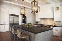 Stunning large gray and ivory kitchen showcases two stunning mercury glass ball lanterns hung from a shiplap ceiling finished with white beams above a gray wash center island accented with a black granite countertop seating three gray rush seat counter stools.