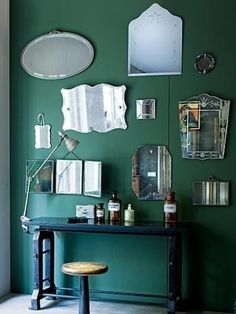 Vintage Billiard Green Walls, Black Drafting Desk, and great Antique Mirrors used as an Art Wall create a Handsome Men's Room.