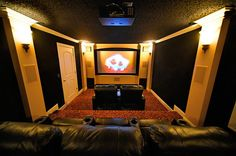 Movie theater room with walk sconces and dark walls and white moldings and accents
