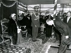The Emperor and Empress of Ethiopia at a public ceremony around 1952  The Ambassador of the United States paying his respects to Her Majesty the Empress as the Emperor looks on.