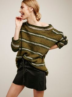 Cozy up in this knit tunic with a cute multi-color striped pattern. Relaxed open neckline creaes a draped off-the-shoulder silhouette. Metal accents along the sleeves.