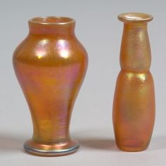 Tiffany Art Glass   Two miniature vases   New York, early 20th century   Bulbous body tapering to circular foot; flared rim on swollen cylindrical body in two parts, both in gold iridescence, polished pontils, marked on base L.C.T. and numbered G2691 and G2644, ht. 3 1/8 and 3 1/4 in.