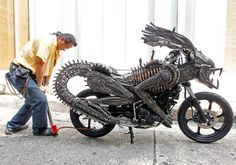 """Artist Roongrojna Sangwongprisarn inflates air into the rear tire of a motorcycle made from recycled materials of spare parts from cars and bicycles at a workshop in Bangkok."""