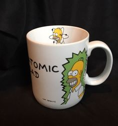 This is a listing for the official Simpsons Atomic Dad mug. Great for any Simpsons fan! Features Homer Simpson glowing green from his job at the nuclear power plant on the outside. On the inside lip there is a smaller homer head with an atomic symbol behind him. Mug has hairline crack on handle but does not effect functionality. See photo. As always&#x3b; please view all photos closely and ask all questions before hitting the buy it now. If you enjoy this item, check out my other...