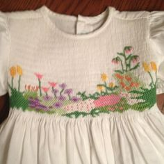 flower garden smocking. wonder if I can do this! It is on the front cover of a book on picture smocking by laura jenkins thompson.