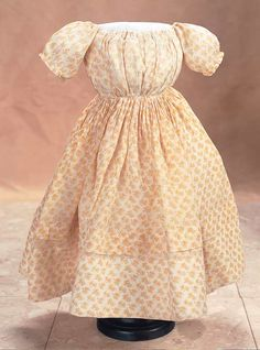 Of very delicate sheer muslin with printed yellow buttercup design, the dress has a rounded neckline, short pouf sleeves, full bodice, cartridge-pleated skirt, adjustable waist by hidden strings, button closure at the back shoulders, and is accented by self-piping at the neckline and waist. Circa 1860.