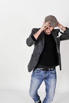 Comprar ropa de este look:  https://lookastic.es/moda-hombre/looks/blazer-jersey-con-cuello-barco-vaqueros-gorra-inglesa-panuelo-de-bolsillo-correa/6804  — Gorra Inglesa Marrón  — Pañuelo de Bolsillo Blanco  — Jersey con Cuello Barco Negro  — Blazer de Lana Gris Oscuro  — Correa de Cuero Negra  — Vaqueros Azules