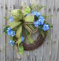 This spring wreath is characterized by realistic blue hydrangea blooms and fern. A beautiful green wired faux silk ribbon is overlaid with a wired burlap mesh ribbon and made into a simple bow. This wreath is perfect to welcome spring and use all summer long! Average Diameter: 23 (tip