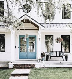 exterior shot of a modern farmhouse with a double turquoise entry door White Farmhouse Exterior, Modern Farmhouse Porch, Turquoise Door, Painted Front Doors, Villa, White Houses, Exterior Colors, House Painting, House Colors