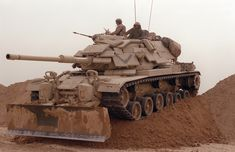 Marines from Company D, Tank Battalion, drive their main battle tank over a sand berm on Hill 231 while rehearsing their role as part of Task Force Breach Alpha during Operation Desert Storm. The tank is fitted with reactive armor and an bulldozer kit. M109, Patton Tank, Tank Armor, Military Armor, Military Tank, Military Surplus, Armored Fighting Vehicle, Military Modelling, World Of Tanks