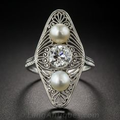 Just over 1 inch long and lovely, this singular, sensational and highly distinctive Edwardian dinner ring features a gorgeous, collet-set European-cut diamond weighing .90 carats. The sparkling stone is accompanied north and south by a lustrous pair of natural pearls, all of which are set vertically atop an elongated lozenge shape top intricately adorned with platinum filigree.