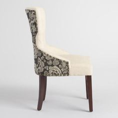 With a curvy, keyhole silhouette, our Black Floral and Linen Maxine Dining Chair brings stylish sophistication to any space. Upholstered with solid linen on one side and a dramatic floral print on the back, this chair is framed by nail heads that emphasize its rich upholstery.