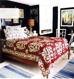 The red bedspread is what attracted me to this bedroom.  That plus the navy walls and the blue stripped rug. I could live in that room.