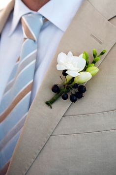 A boutonniere of freesia and hedera berries adds the perfect touch of outdoor elegance to the groom's tan suit.
