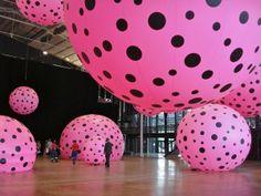 La halle de La Villette est envahie d'énormes ballons roses à petits pois noirs. Flottant au-dessus des têtes ou ancrés au sol, les ballons forment une environnement onirique et joyeux. Comme dans une volière, les pois roses se balancent doucement au passage des visiteurs, bercés par la voix de Yayoi Kusama, la créatrice de l'installation « Dots Obsession », l'obsession des pois.