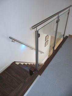 Glasbalustrade tegen de verdiepingsvloer gemonteerd in combinatie met een RVS leuning met verlichting.   LED illuminated handrail and balustrade