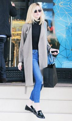 Elle Fanning wears a turtleneck, neutral trench coat, cropped jeans, round sunglasses, and Chanel loafers