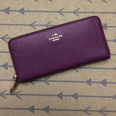 """coach side zip wallet NWT Coach hard leather side zip wallet. Color is a plum purple with gold hardware, classic emblem on front with plain back. Inside has zip compartment in middle opening up either side for cash/ checks as well as four card holders on each side and places for cash attached to each of the sides of the wallet. Dimensions are approximately 7""""x3"""" Coach Bags Wallets"""