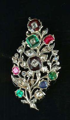 A 19th century diamond and gem-set brooch the openwork foliage set with cushion-shaped and rose-cut diamonds, with emerald, sapphire and garnet buds, the larger stones inset with cushion-shaped diamonds, in closed back settings, length 5.5cm.