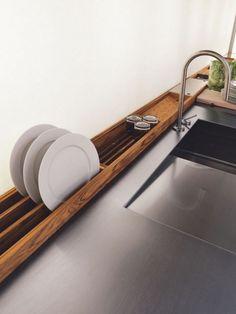 Voici un concept d'égouttoir pour la cuisine qui est très bien pensé puisqu'il se positionne derrière l'évier et occupe ainsi une place inutilisée dans la cuisine. Avouez aussi que l'ensemble en bois apporte de l'esthétisme au plan de travail. Cet égouttoir est proposé par Riva 1920.: